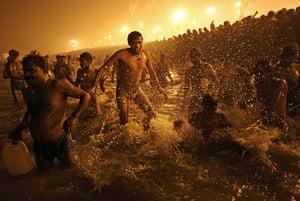 Kumbh Mela: An Indian Hindu man jumps up and down in the water at Sangam