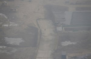 Air Pollution in China: Workers walk at a construction site in the heavy haze in Beijing