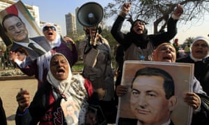 Supporters of former president Hosni Mubarak celebrate outside the military hospital where he is currently held after a Cairo court ordered his retrial on Sunday.