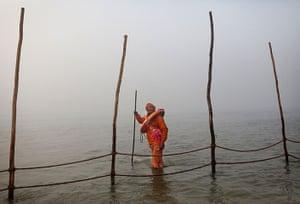 Kumbh Mela: A Hindu volunteer carries a life preserver