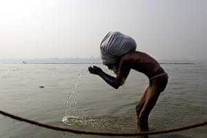 Kumbh Mela: An elderly devotee, with a huge turban, offers his prayers