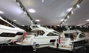 Sales assistants wait by powerboats on the Sunseeker stand at the 2013 London Boat Show, which is being held at the ExCeL Centre until January 20.