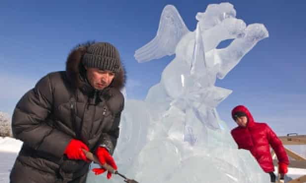 """Frozen tiger - hidden dragon: Sculptors make a final touch to their creation during ice and snow sculptures festival at the """"Eight Lakes"""" Park-Resort outside Almaty, Kazakhstan."""