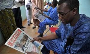 Mali man reads newspaper praising France