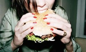 Young woman biting into burger