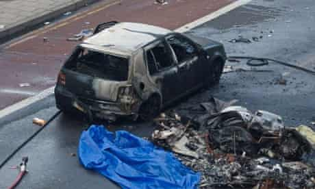 Debris and a fire damaged car are pictured at the scene of a helicopter crash in central London.
