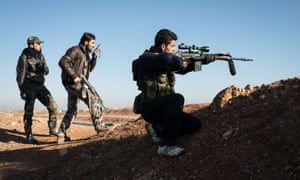 A Syrian rebel sniper takes aim at pro-government forces near the Abu Baker brigade in Albab, 30 kilometres from the northeastern Syrian city of Aleppo, on 16 January 2013.