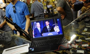 Customers shop for weapons at the Bullet Hole in Sarasota, Florida as they listen to an announcement about gun control by President Obama.