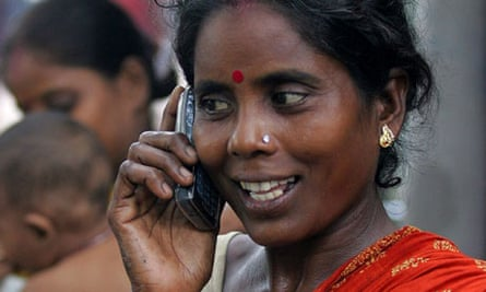 Indian slum dweller uses mobile phone in Kolkata