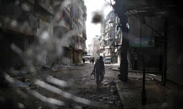 A fighter from the Islamist Syrian rebel group Jabhat al-Nusra is seen through a smashed bus window in Aleppo.