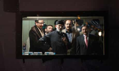Tahir-ul-Qadri (centre) addresses his supporters from behind the window of his bomb-proof box