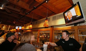 People at the Wasatch Brew Pub listen to Lance Armstrong being interviewed by Oprah Winfrey, about his drug use in Park City, Utah.