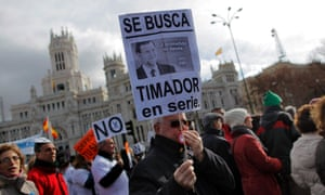 "A protestor carries a banner reading, ""Spanish Prime Minister Mariano Rajoy, serial fraudster"" during a demonstration last Sunday."