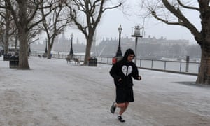 A man jogs in the snow in London.