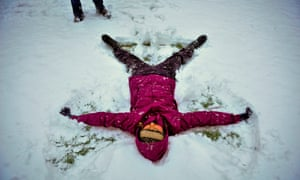 A woman makes a snow-angel in the snow in Bristol, as snow shut roads and disrupted train travel today but the major commuter belt areas of southern England escaped the worst of the morning hazards.