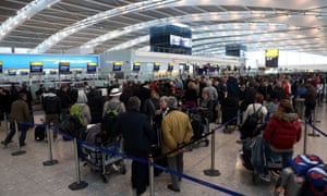Crowds wait at check in at Heathrow Terminal 5 as Britain s transport network began to buckle as heavy snow swept the UK.