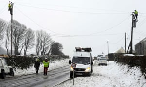 Engineers repair a power cable that had fallen onto a road during a heavy snowfall near Narberth, west Wales January 18, 2013.
