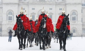 Members of the Household Cavalry Mounted Regiment cross Horse Guards Parade in the snow in central London January 18, 2013.