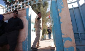 An Algerian guard gestures at the main entrance of a hospital in In Amenas, as people wait to know the fate of their relatives who were taken hostage by Islamist militants in a gas facility, January 18, 2013.
