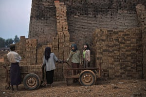20 Photos: Workers stand by piles of bricks at a factory on the outskirts of Yangon