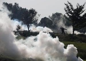 20 Photos: A Palestinian protester hurls a stone at Israeli officers near Ramallah