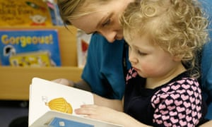 Catherine Gaffey holds little girl while reading to her