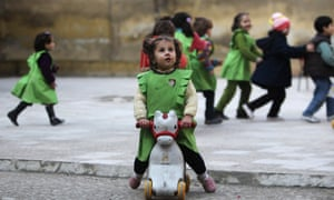 A girl looks up to the sky after hearing the sound of shelling in the playground of al-Tawheed school in Aleppo on 1 January.