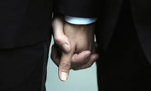 Two married men hold hands as they prepare to retake their vows