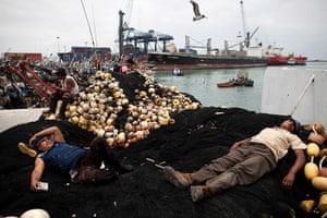 FTA: Rodrigo Abd: Fishermen rest on their docked fishing vessel at the port in El Callao