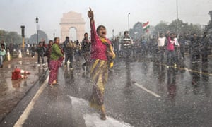 A protester is hit by a police water cannon as she demonstrates in Delhi.