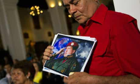 A supporter of Chavez holds a picture of him