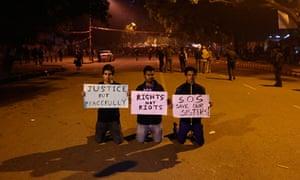 Three demonstrators call for calm in Delhi.