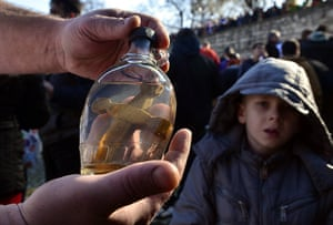 24 hours: Skopje, Macedonia: A man closes a bottle with a wooden cross