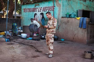 24 hours: Niono, Mali: A French soldier sends a text message in front of a restaurant