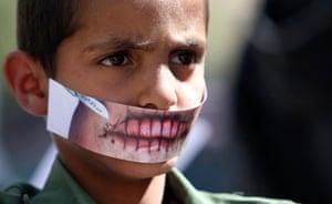 24 hours: Sana'a, Yemen: A boy wears a paper mask to depict silence