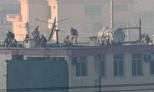 Security personnel are seen on the roof of the Afghan police headquarters during an attack in Kabul. NATO troops joined a fire-fight against a Taliban suicide squad that stormed a Kabul police headquarters.