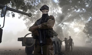 A French soldier wearing a skeleton mask stands next to a tank in a street in Niono, Mali. David Cameron has pledged to support French efforts.