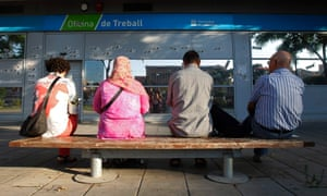 People wait for the opening of an employment office in Badalona, near Barcelona.