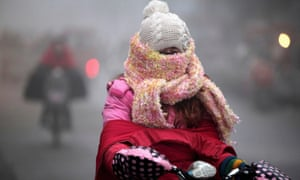 Impressively wrapped up against the cold a woman cycles along a street in the fog in Haozhou in China.