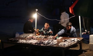 Palestinian boys sell fish on the beach in Gaza City upon their return from a fishing trip.