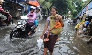Residents wade through a flooded neighbourhood to reach relief distribution centres in Jakarta. Indonesia's National Disaster Mitigation Agency said more than 30,000 people have been displaced during the widespread flooding as forecasters predict more rains to come.