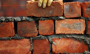 A labourer lays bricks on a wall