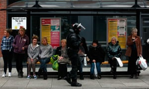 A police officer in riot gear at a bus stop in Belfast