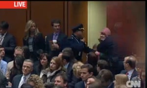 Guards remove a protester, in the pink hat, from the Kerry hearing in a screen grab from CNN