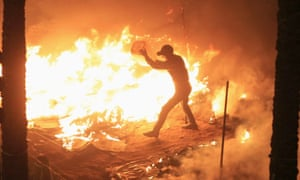 An anti-Morsi demonstrator tries to douse flames from a burning tent set alight by riot police at Tahrir Square in Cairo on Thursday night.