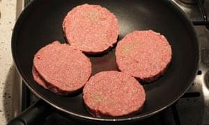 Four Tesco burgers frying in a pan