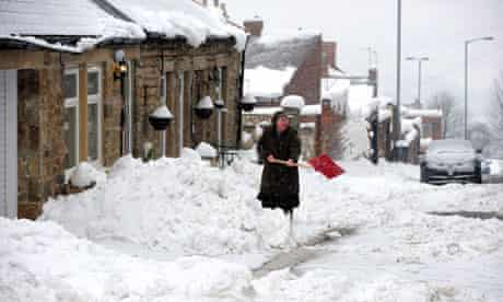 A woman clears the snow in Tanfield, County Durham