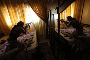 20 Photos: a rebel fires his Draganov sniper rifle in the Mleha suburb of Damascus