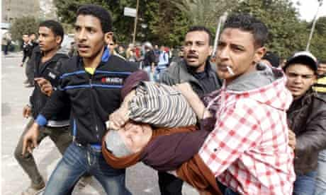 Protesters near Tahrir Square in Cairo help a woman overcome by teargas