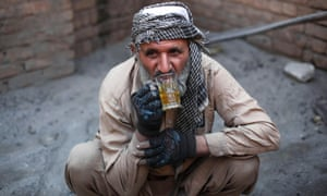 Uais Khan, 62, drinks green tea during a break at a factory in Rawalpindi. The factory cooks corn overnight in heated salt and sand before they are sold as a popular street food dish.